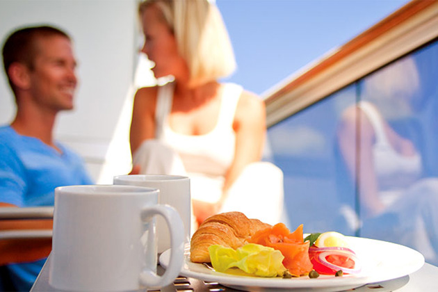 Couple eating breakfast on cruise balcony