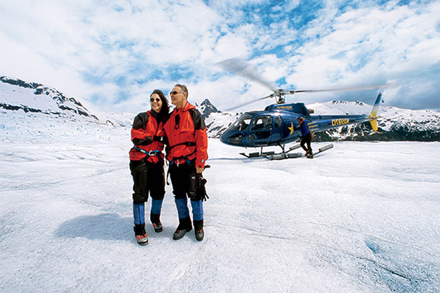 Passengers exploring a glacier on a helicopter excursion<br>