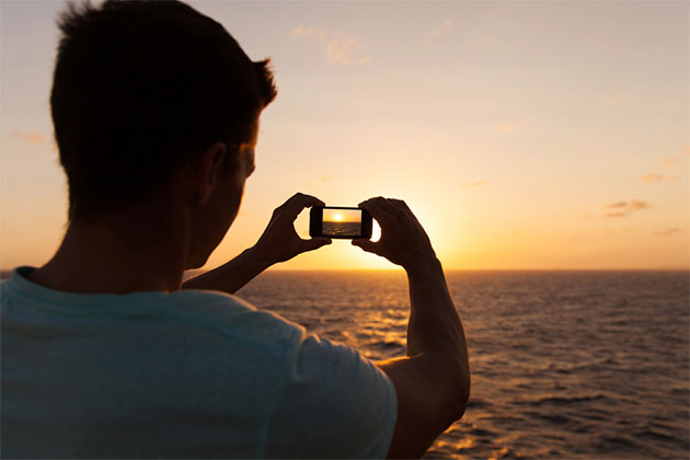 Man taking a picture of the sunset on a cruise