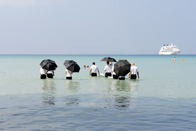 Seabourn officers with umbrellas pushing a cooler out to water