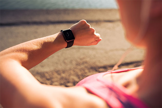 Woman checking her watch on the beach