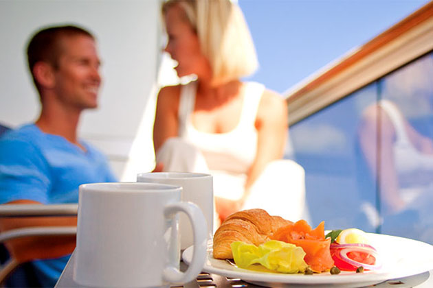 Couple eating room service on cruise balcony
