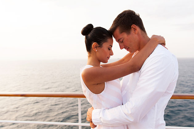 young couple hugging with eyes closed on a cruise ship