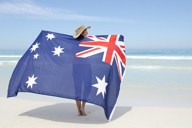 woman wearing akubra hat and with Australian flag around shoulder standing at tropical Australian beach