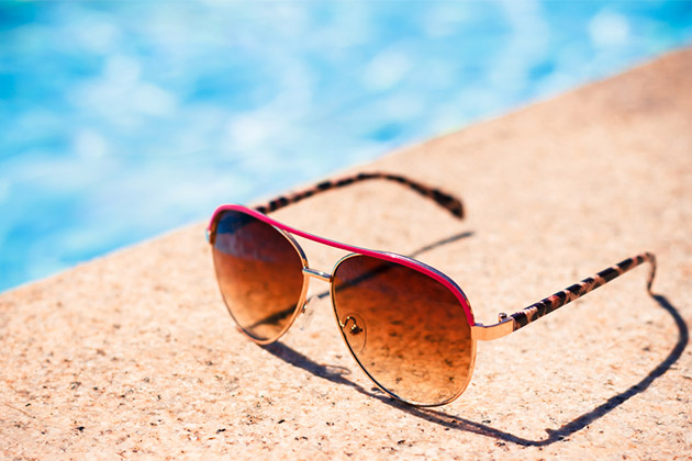 Brown funky sun glasses near swimming pool
