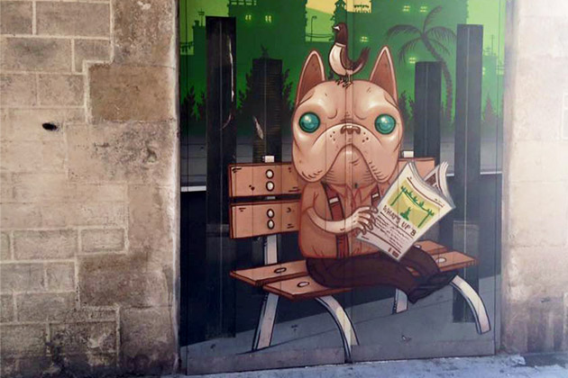Graffiti of a cartoon dog reading the paper on a park bench