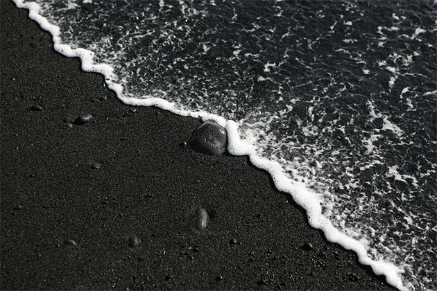 Black sand beach with wave