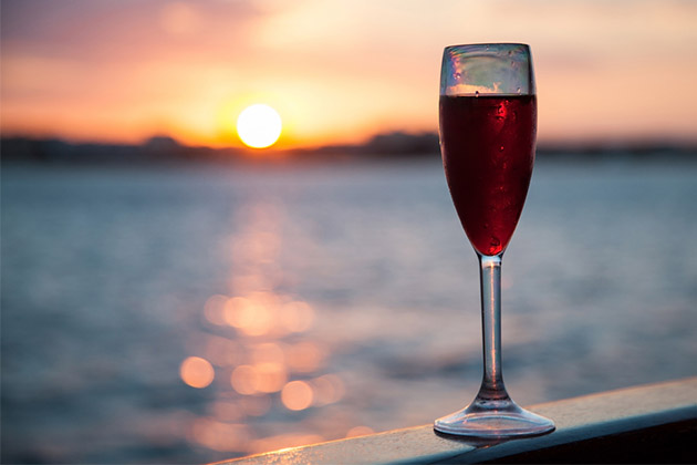 Goblet with red wine on ocean or river background