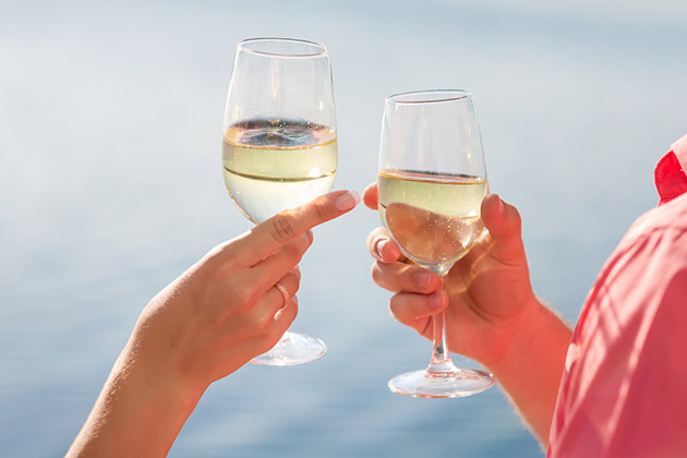 Close up of happy couple drinks champagne on a yacht