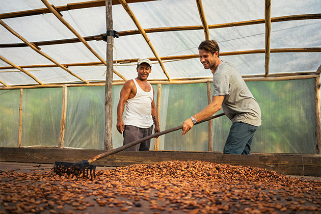 Fathom passenger raking cacao beans at a nusery in the Dominican Republic
