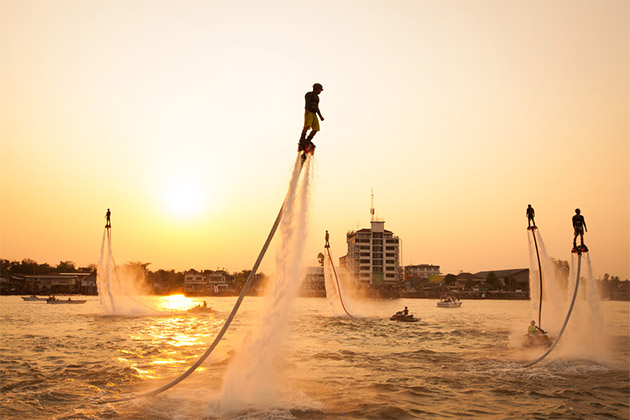 Silhouettes of flyboarders at sunset