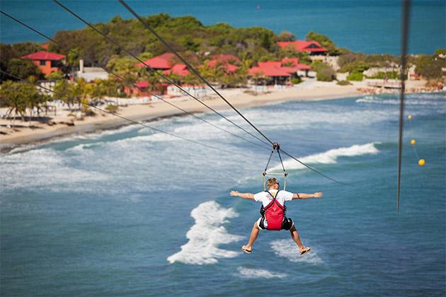 Man ziplining over the water in Labadee