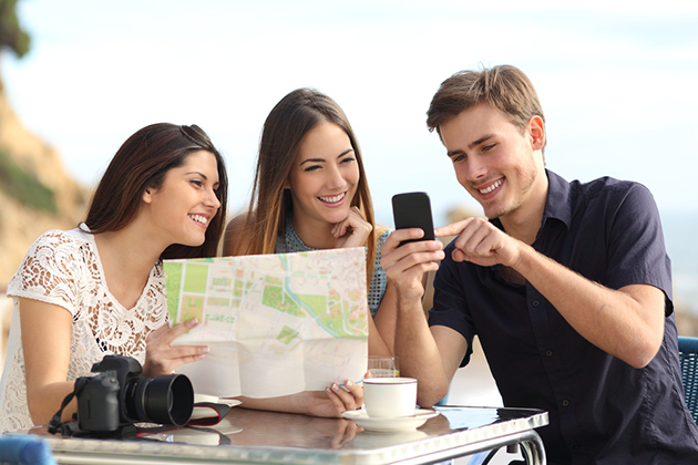 Group of young tourist friends consulting gps map in a smart phone in a restaurant with the beach in the background