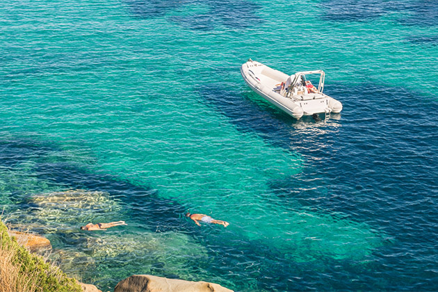 Couple snorkeling in turquoise tropical water among a small boat