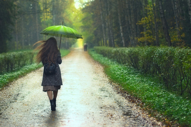 Girl under holding an umbrella in the rain