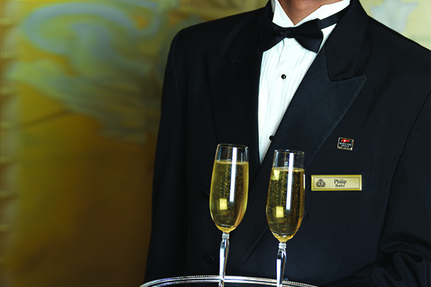 Cunard butler in tuxedo serving two glasses of Champagne on a platter