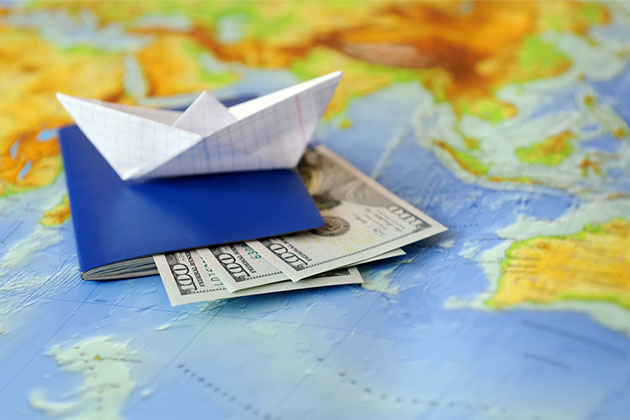 Paper boat with passport and $300 placed on top of a world map