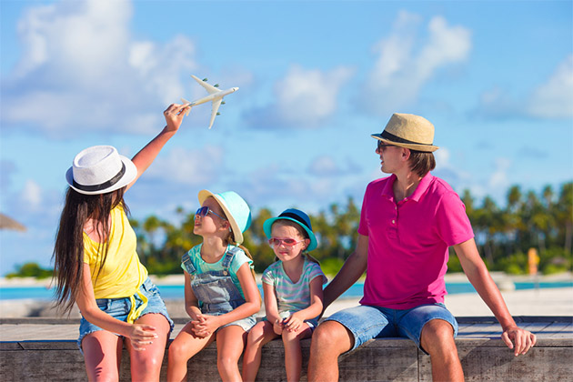 Family in tropical destination flying a toy plane