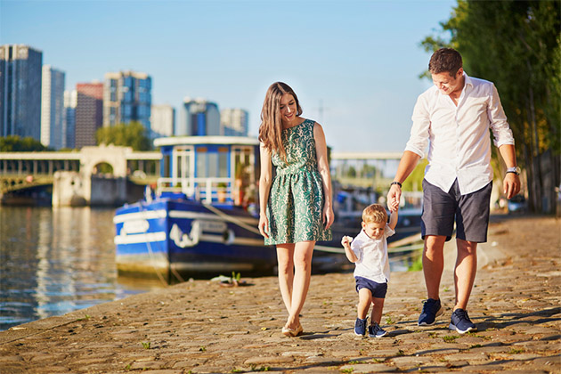 Family of three ambling along the cobblestone streets of Paris