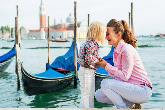 Mother and daughter in front of gondolas in Venice