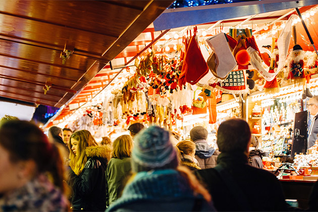 Busy Christmas Market Christkindlmarkt in the city of Strasbourg, Alsace region, France with people admiring Christmas gifts