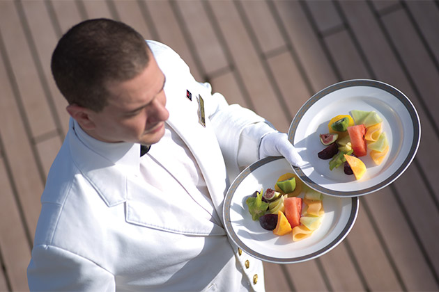 Luxury cruise waiter carrying two plates of fresh fruit