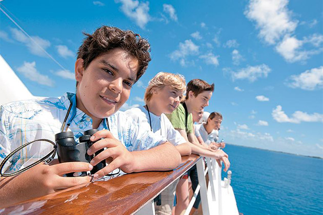 Kids looking out over a cruise deck railing on a Paul Gauguin ship