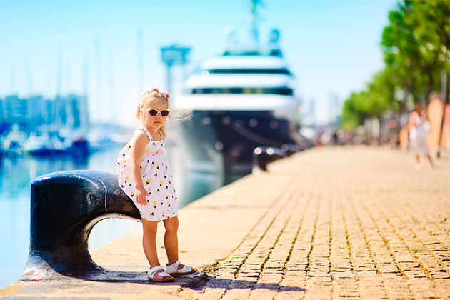 Little girl in port with a luxury liner ni the backgroun