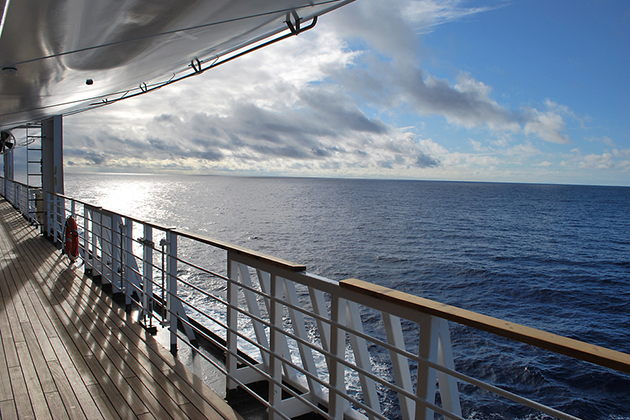 Ocean view from a cruise ship deck on a bright day with blue skies and clouds in the Pacific ocean