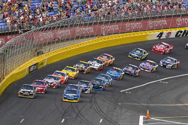 Race cars round turn on track with fans in the background