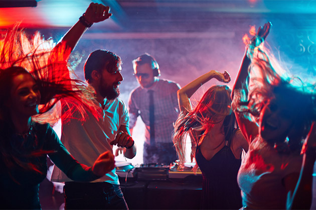 Group of friends dancing in a nightclub with a DJ