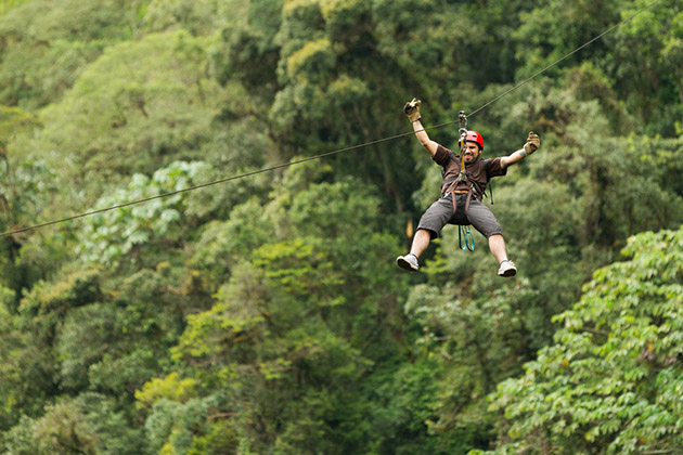 Man zip lining in the rainforest