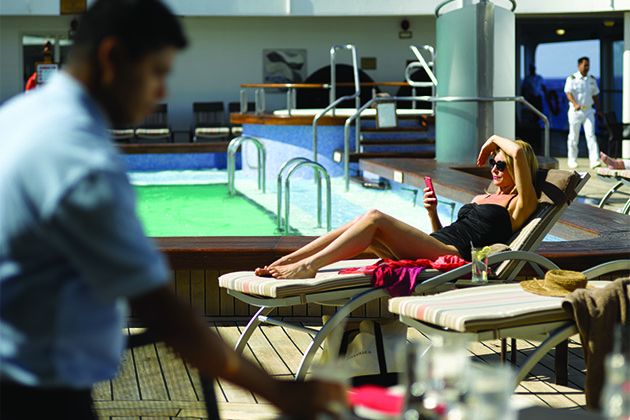 Woman lounging by the pool on a Siversea cruise ship