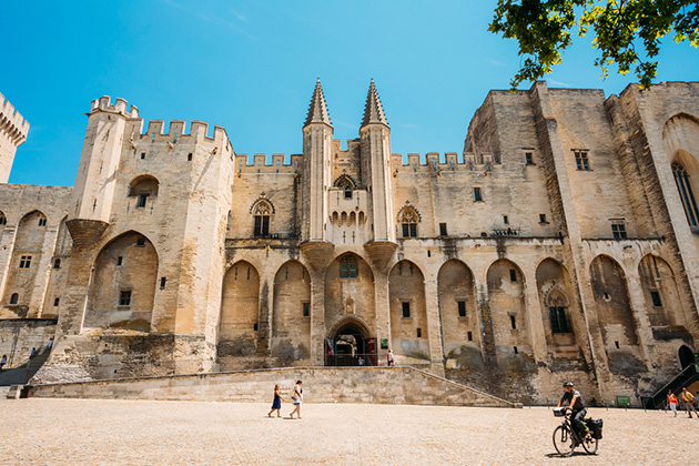 People walking near ancient Popes Palace, Saint-Benezet, Avignon, Provence, France.