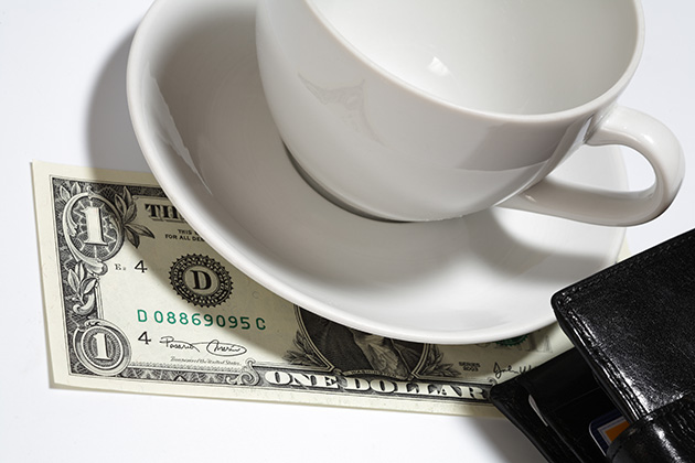 one dollar tip under coffee cup