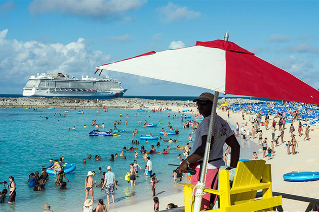 A beach lifeguard in Great Stirrup Cay with Norwegian Breakaway docked in the background