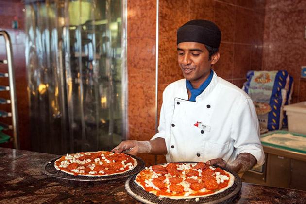 Exployee serving pizza on Carnival Conquest