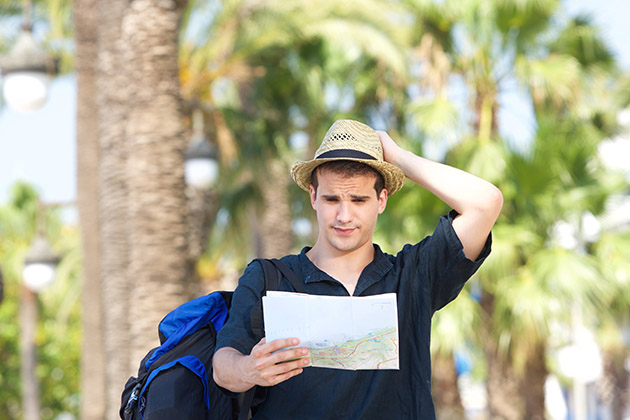 Portrait of a lost tourist with bag holding map