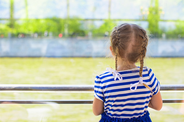 Little girl looking over the river from luxury ship