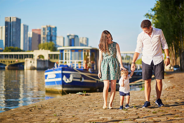 Happy family of three enjoying their vacation along the waterfront in Paris, France