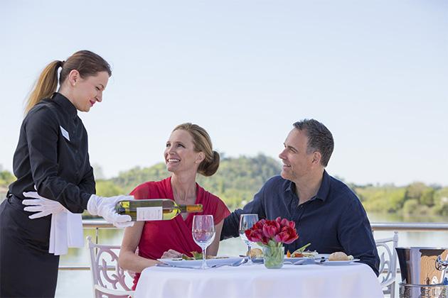 Uniworld crew member serving passengers wine at dinner