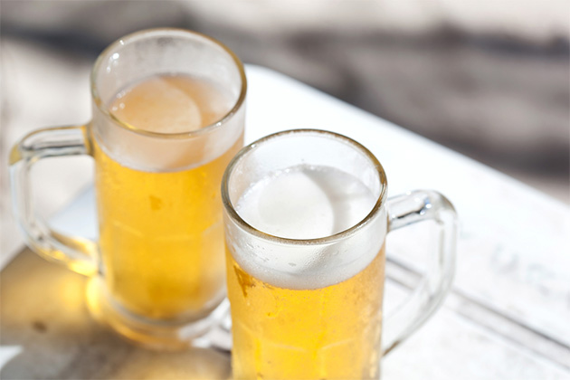 Glasses of cold beer on white wooden table, nobody