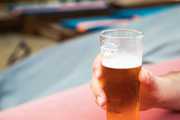Closeup of a male hand holding a glass of beer on the beach.