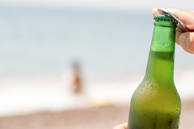 macro photography of a beer with a beach background