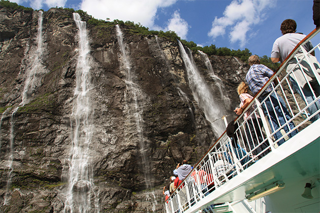 People gazing above at Geiranger fjord's waterfalls from a Hurtigruten cruise deck