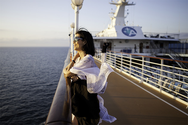 Woman watching the sunset from an Azamara pool deck