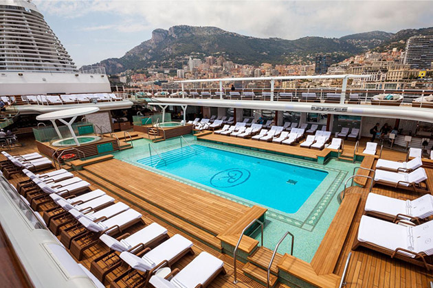 Shot of Seven Seas Explorer's pool deck, with port in the background