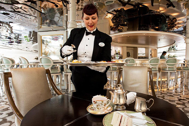 Female crew member serving afternoon tea and canapes on Crystal Symphony