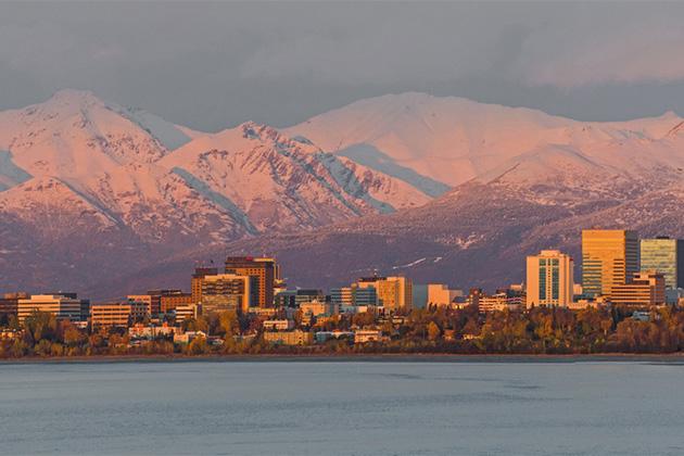 Anchorage, Alaska at sunset below the snowy Chugach Mountains