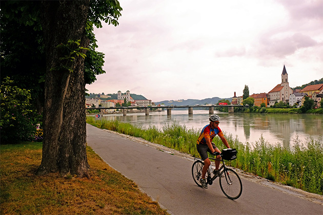 Man biking along the river in Europe